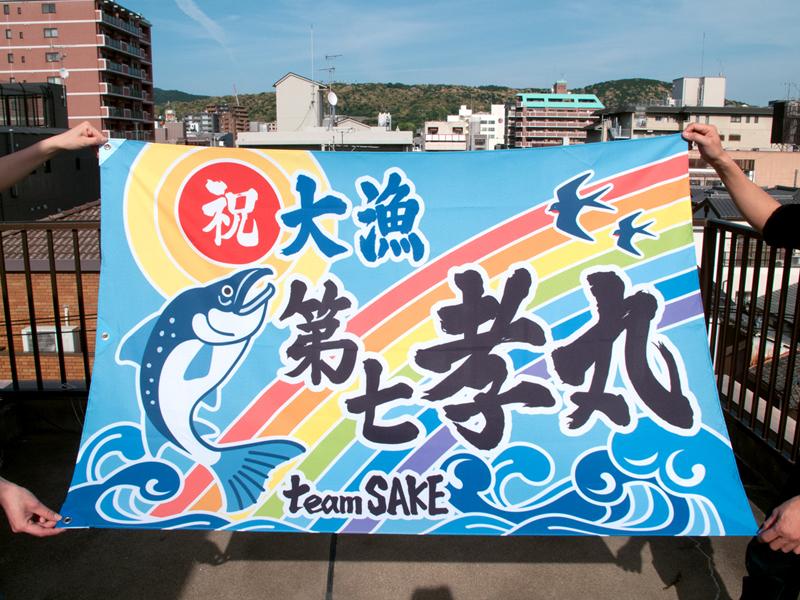 大漁旗の写真。水色基調の旗にサケ、虹が描かれている